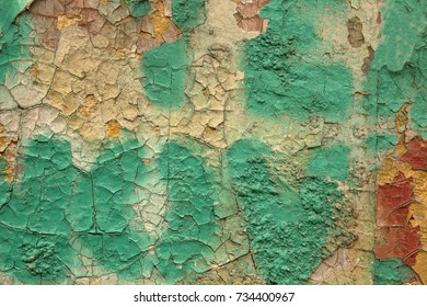 An old colored cracked dilapidated wall in the industrial zone of an abandoned factory useful as background.