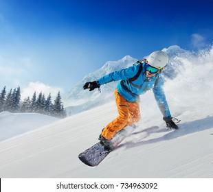アルプス山脈の斜面を駆け下りる青年スノーボーダー。ウィンタースポーツとレクリエーション、レジャーアウトドアアクティビティ。
