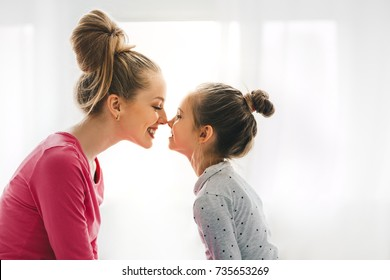 Mutter und Tochter spielen und küssen, Zusammengehörigkeitskonzept. Liebevolle Familie