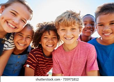 Schließen Sie oben von jugendlichen Freunden in einem Park, der zur Kamera lächelt