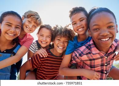 Sechs jugendliche Freunde huckepack in einem Park, Nahaufnahmeporträt