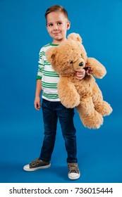 Porträt in voller Länge eines lächelnden kleinen Jungen, der Teddybär hält und weg lokalisiert über blauem Hintergrund schaut