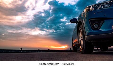 有體育的藍色緊湊SUV汽車和現代設計在混凝土路在海邊停放了在日落。環保技術。停車場。混合動力和電動汽車技術概念。