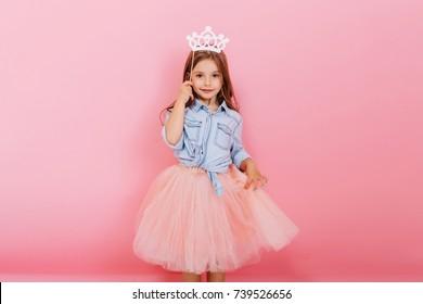 Niña alegre con cabello largo morena en falda de tul con corona de princesa en la cabeza aislada sobre fondo rosa. Celebrando el carnaval brillante para niños, fiesta de cumpleaños, divertirse con un niño lindo