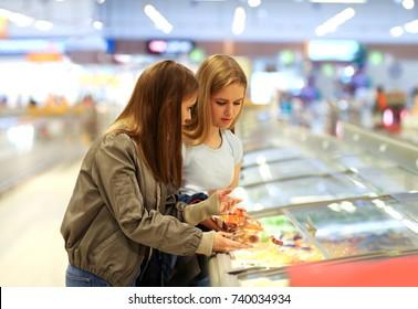 Two girls choosing frozen food from a supermarket freezer