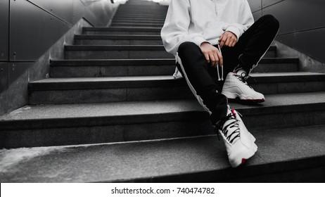 Mann sitzt auf der Treppe. Lifestyle-Fotografie. Städtische Tapete. Innenplakat. Schau Buch. Hype-Turnschuhe. Beste