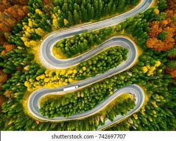 秋の色の森の中の曲がりくねった道を曲がりくねった大型トラックの空撮