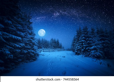 La luna llena se eleva sobre el bosque de invierno cubierto de nieve fresca. Vía láctea brillante fantástica en un cielo estrellado. Nochebuena.
