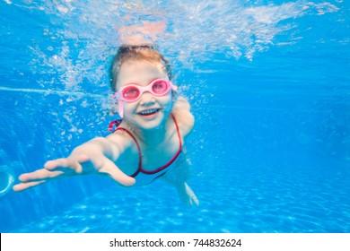 Porträt des kleinen Mädchens, das unter Wasser im Pool schwimmt