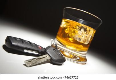 Alkoholische Getränke und Autoschlüssel unter Scheinwerferlicht.