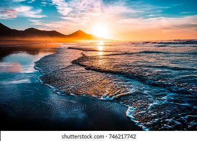 Impresionante puesta de sol en la playa con un horizonte interminable y figuras solitarias en la distancia, e increíbles olas espumosas. Colinas volcánicas en el fondo.