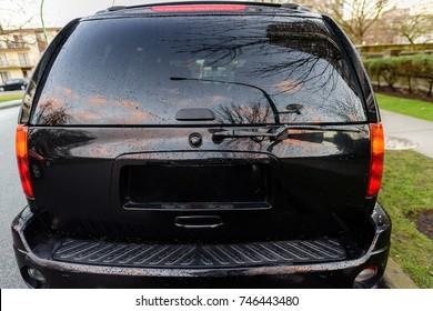 Heckscheibe des Autos Rückansicht eines schwarzen Autos, das an einem Sommerabend in einem Stadtparkplatz geparkt wird.