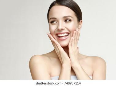 側に見て笑って頬を押しながら幸せな美しい女の子。きれいな女性の清潔でさわやかな肌。表情豊かな表情。美容、美容、スパ