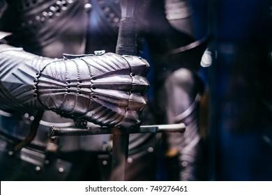 Nahaufnahme einer mittelalterlichen Stahlrüstung mit Hand, die ein Riesenschwert hält
