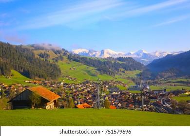 Casa de cabaña de troncos suizos y casa de madera Pueblo suizo en vista de hierba verde con fondo de montaña de los Alpes a lo largo de la línea panorámica Golden Pass, Zweisimmen a Montreux, Suiza.