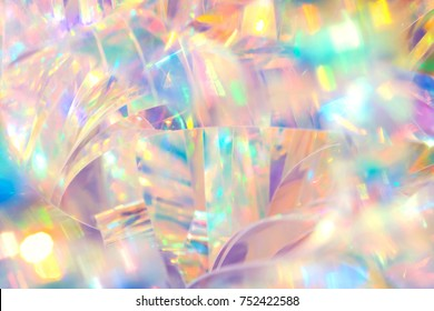 Abstract radiant cheerful disco fun wallpaper image of festive holographic foil ribbon with bright gleaming pastel colored sparkling crystal reflections and blurred bokeh light effect