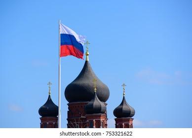 Russische Flagge flattert neben Kirchenkuppeln - Symbol für das Verhältnis von Staat und Religion