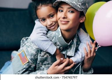 自宅で風船で軍服を着て母親を抱き締めるアフリカ系アメリカ人の娘