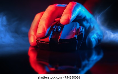 Nahaufnahme von Hand over Wireless Game Mouse auf dunklem Hintergrund und Rauch; Der Finger ist bereit zu klicken