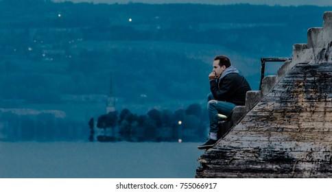 Mann, der in der Dämmerung am Dock sitzt und über den Sinn des Lebens nachdenkt. See, Landzunge mit Kirche und Hügeln im Hintergrund.