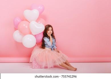 Feliz imagen brillante de linda niña alegre en falda de tul sentada en el presente con globos aislados sobre fondo rosa. Increíble cumpleaños encantador niño de moda mirando a la cámara
