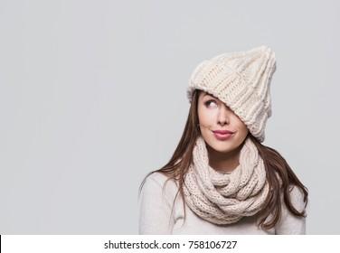 Schöne Frau, die aufschaut. Auf grauem Hintergrund isoliert. Lächelndes Mädchen, das warme Kleidung, Winterporträt trägt