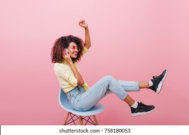 Retrato interior de cuerpo entero de niña africana confiada en camisa rosa con patineta. Entusiasta mujer negra con peinado rizado posando en estudio con interior azul. en zapatilla negra