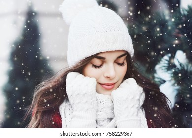 Nahaufnahmeporträt des jungen schönen glücklichen lächelnden Mädchens im Freien, das weiße Strickmütze, Schal und Handschuhe trägt. Modell posiert in der Straße. Winterferienkonzept. Getönt
