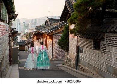 Stražnji dio dviju žena u hanboku šetajući kućama u tradicionalnom stilu sela Bukchon Hanok u Seulu u Južnoj Koreji.