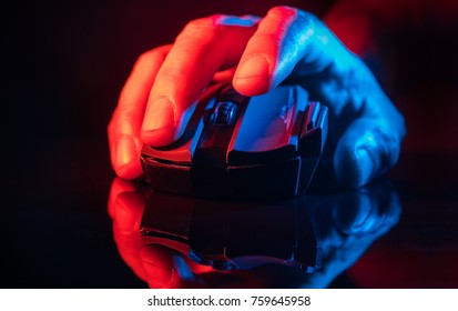 Close up of Hand over wireless Game Mouse on dark background ; The finger ready to click