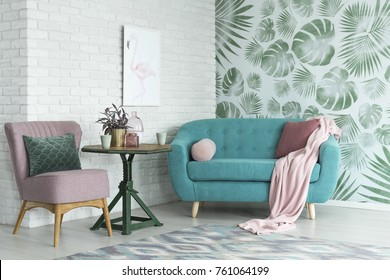 Groene tafel met een plant tussen roze stoel en blauwe bank in bloemenwoonkamer met behang en poster