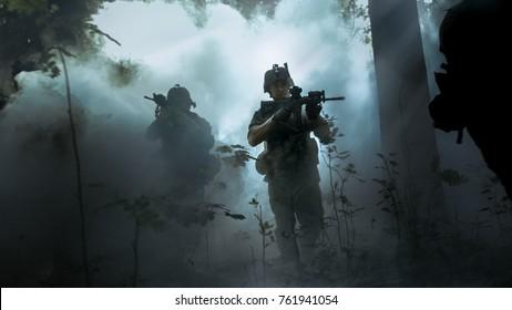 Voll ausgerüstete Soldaten in Tarnuniform, die den Feind angreifen, Gewehre, die schussbereit sind. Militäroperation in Aktion, Trupp läuft in Formation durch kalten, dichten Rauchwald.
