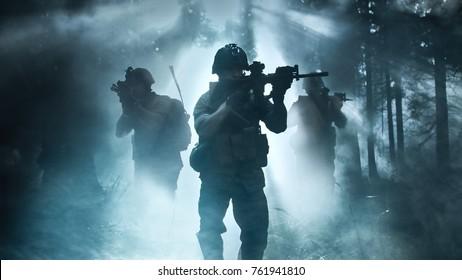 Silhouette des voll ausgestatteten Soldaten, der sich durch Smokey Forest mit schussbereitem Gewehr bewegt. Aufklärung Militäroperation. Trupp bewegt sich hinter ihm. Dunkle und kalte Umgebung.