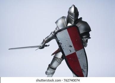Ritter mit Schwert und rotem kariertem Schild auf lokalisiertem Hintergrund