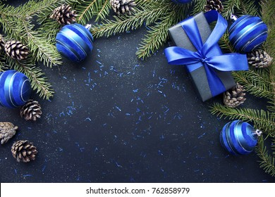Christmas gift with blue ribbon and blue balls, tree branches and cones on dark blue background with copy space.