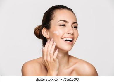 クローズアップ笑って美しい半分裸の女性の顔のクリームを適用し、離れて白い背景で隔離の美しさの肖像画