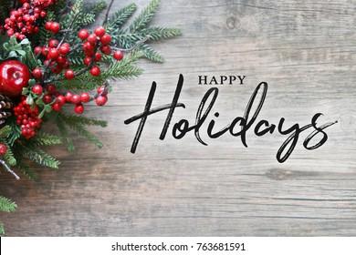 Frohe Feiertage Text mit immergrünen Weihnachtszweigen und Beeren in der Ecke über rustikalem hölzernem Hintergrund