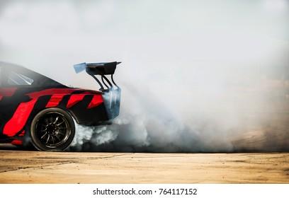 スポーツカーホイールドリフト。スピードトラックで燃えているタイヤからの煙の多い画像拡散レースドリフトカーのぼやけ。スポーツコンセプト、ドリフトカーコンセプト