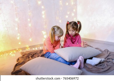 Cute little girls play in computer games on device or watch cartoons, press something on touch screen of tablet, smile and communicate with each other, sitting on rug in bright room with flickering
