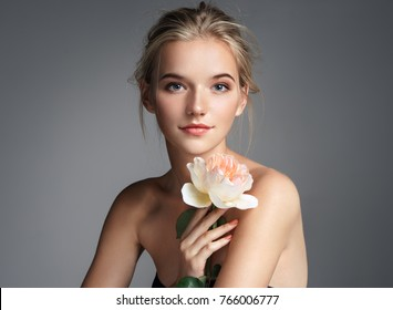 完璧なメイクで魅力的な若い女の子。灰色の背景にローズとブロンドの女の子の写真。スキンケアのコンセプト