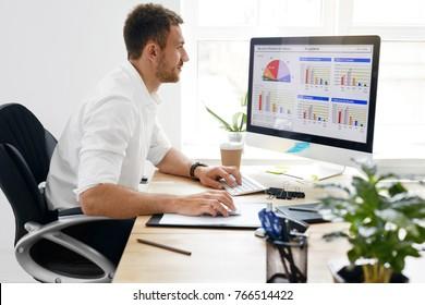 Hombre de negocios joven que trabaja en la computadora en oficina. Retrato del hombre de negocios hermoso en la camisa blanca que se sienta en el escritorio del trabajo que mira el monitor. Imagen de alta calidad.