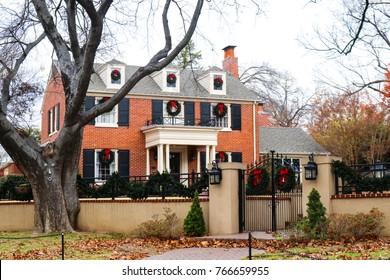 クリスマスの花輪で美しく装飾された鉄の柵と門のある高級な緑豊かな住宅地区にある2階建ての赤レンガ造りの家
