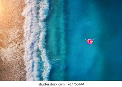 オルデニズの透明なターコイズブルーの海でピンクの浮き輪で泳いでいる若い女性の空撮。女の子、ビーチ、美しい波、日没時の青い水と夏の海の景色。ドローンからの上面図