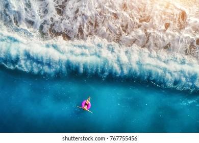 Luftaufnahme der jungen Frau, die auf dem rosa Schwimmring im transparenten türkisfarbenen Meer in Oludeniz schwimmt. Sommerseelandschaft mit Mädchen, Strand, schönen Wellen, blaues Wasser bei Sonnenuntergang. Draufsicht von der Drohne
