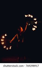Young woman spinning fire in the dark