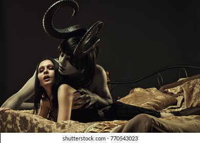 Gehörnter schrecklicher Dämon und gotisches Mädchen im Bett