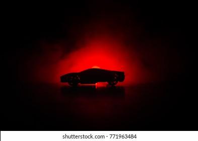Das Auto im Schatten mit leuchtenden Lichtern bei schwachem Licht oder Silhouette des dunklen Hintergrunds des Sportwagens. Selektiver Fokus