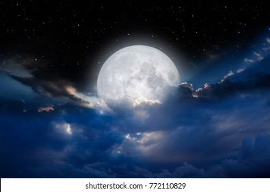 """Night sky with full moon in the clouds """"Elements of this image furnished by NASA"""