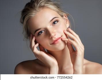 彼女の唇に触れる魅力的な若い女の子。灰色の背景に完璧な肌を持つブロンドの女の子の写真。ビューティー&スキンケアのコンセプト