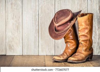 ワイルドウェストのレトロなカウボーイハットと木の床の古い革のブーツのペア。ヴィンテージスタイルのフィルタリングされた写真